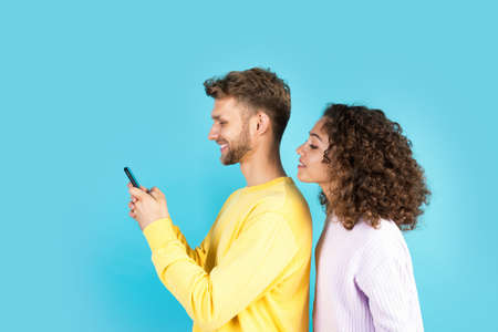 African american girlfriend peers through the back of her boyfriend while he using online app on modern smartphone. Mixed race friends standing on blue copy space background, reading internet news 版權商用圖片