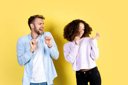 Two people listening music and celebrate on birthday party. Smiling afro american woman dancing with happy european man while they moving together and standing on yellow background with copy space
