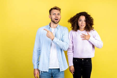 Sale and discount concept. Shocked mixed race friends standing together on yellow background with copy space and looking at camera. Excited man pointing with finger at advertising