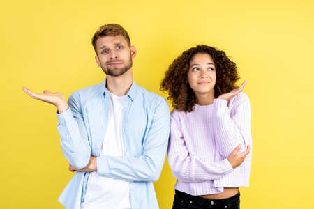 Thoughtful mixed race friends isolated on yellow background with copy space, making thinking faces. Unsure millennial man looking at camera while minded afro american woman standing aside