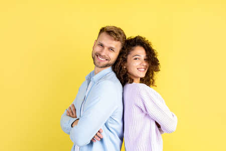 Concept of confident people. Happy afro american woman and smiling european man looking at camera, standing back to back on yellow background with copy space 版權商用圖片