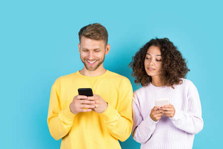 African american woman peep at modern smartphone of her man standing close to boyfriend on blue copy space background. man using online app and wireless internet