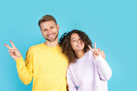 Happy man and smiling african american woman hugging and showing victory sign, standing on blue background with copy space. Charming interracial couple spending time together
