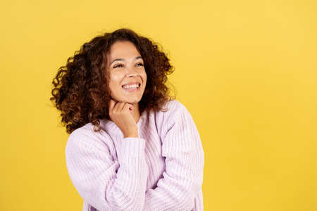 Facial expression concept. Portrait of happy adult afro american woman in cozy pullover laughing, looking aside and standing on yellow copy space background