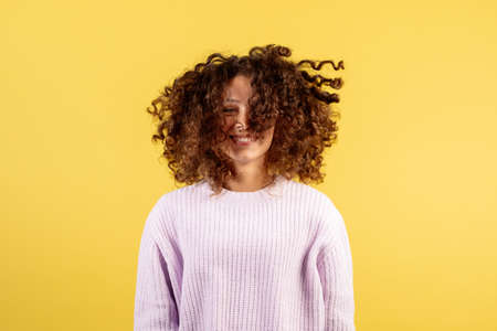 Haircare and wellness concept. Happy young afro american woman with curly wavy hair shaking head, having fun, smiling wide, standing on yellow copy space background