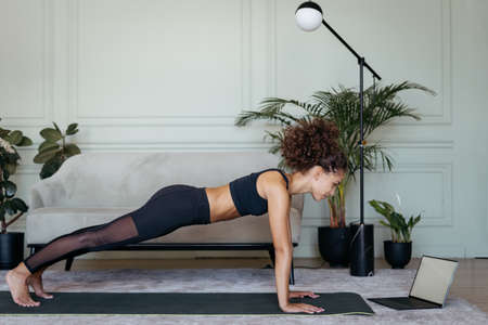 Concept of morning and weekend workout. Serious young afro american sportswoman standing in plank position on yoga mat, watching online video on laptop computer with sport exercise, training at home 版權商用圖片