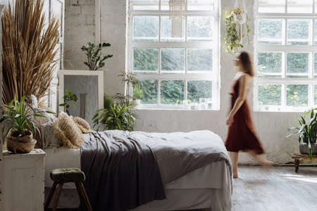 Blurred silhouette of young adult woman walking at comfortable bedroom with interior design in boho chic style. Lady in dress standing near cozy bed, enjoying morning at home 版權商用圖片