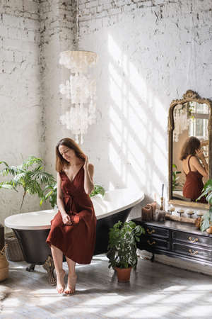 Concept of morning routine. Vertical view smiling young woman sitting on classic bath at comfortable bathroom with green houseplants in flower pots, decor at commode and interior design in boho style