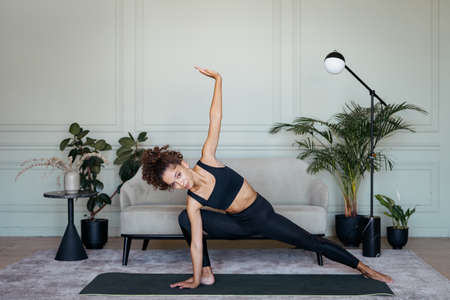 Hatha yoga concept. Confident young athletic afro american woman making sport exercise on mat, stretching body training in living room at home