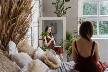 Back view of happy young adult woman sitting on comfortable bed, looking in mirror, spending morning at cozy bedroom with interior design in bohemian style, looking on reflection and smiling wide 版權商用圖片