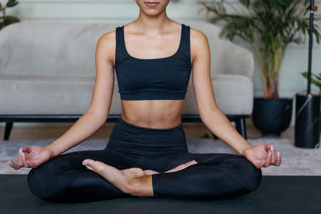 Concept of healthy body and soul. Cropped view of sportive african american woman meditates on yoga mat, making mudra gesture, sitting in lotus after sport exercise training at home