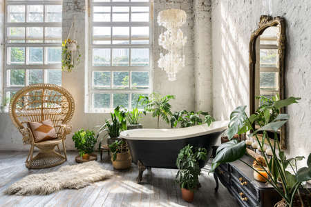 Comfortable bathroom with interior design in boho chic style, bathtub, vintage commode with mirror, wicker armchair, fluffy carpet and green houseplants in flowerpots 版權商用圖片