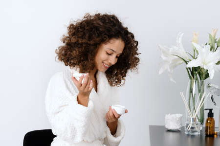 Concept of beauty procedure at home. Side view of happy young african american woman holding container with moisturizing cream in hands, sitting in bathrobe at bathroom ad smiling wide