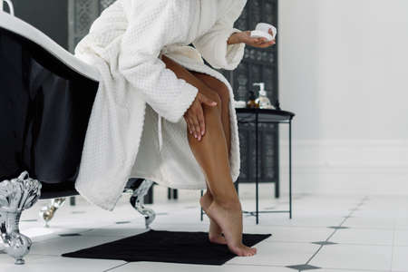 Concept of beauty procedure. Cropped view of afro american woman in bathrobe spending morning in bathroom, applying cream on shaved and soft legs