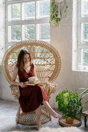 Vertical view of happy young adult woman sitting in wicker armchair, turning pages in book, reading literature, smiling, spending morning at comfortable living room with interior design in boho style