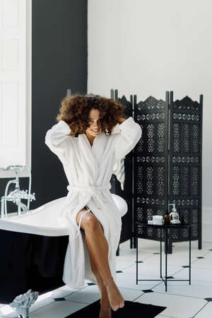 Concept of morning shower and everyday routine. Vertical view of happy and smiling young afro american woman in bathrobe looking at camera, spending time in bathroom