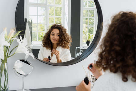 Calm young adult afro american woman in bathrobe looking on mirror reflection at bathroom, holding pipette with natural serum oil near bottle with natural organic cosmetics
