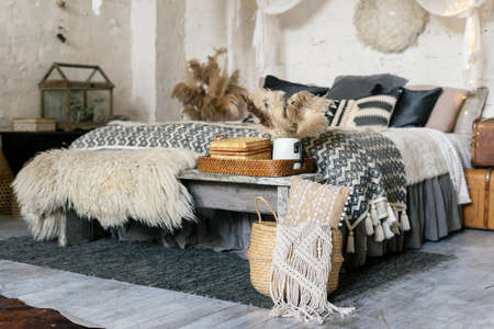 Cozy bedroom with boho style interior, carpet near comfort bed, plaid, pillows and blanket, wooden bench seat, dry plants in vase, home decor in wicker basket