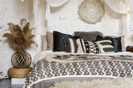 Concept of hygge interior in cozy bedroom. Eco friendly home decor and dry plants in ethnic vase near soft comfort bed with warmth plaid and pillows