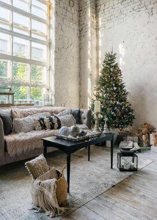 Vertical photo of cozy living room with soft cushions on comfortable couch and new year decoration at christmas tree. Modern apartment with loft interior design