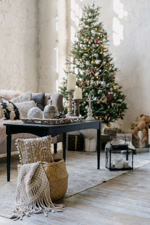 Selective focus on woven basket with plaid against new year tree on blurred background. Vertical photo of cozy living room with winter decor, comfort sofa and coffee table