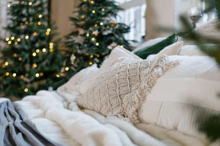 Beautiful cozy bedroom in winter style interior, comfort bed and traditional holiday decor at home against blurred background with garland lights on decorated new year tree 版權商用圖片