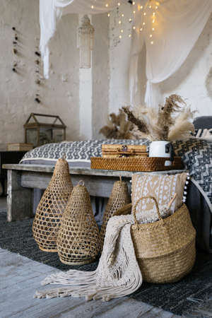 Still life concept. Close up view of wicker basket with plaid, pillows and home decor near wooden bench seat. Comfort bed in cozy bedroom with boho style interior 版權商用圖片