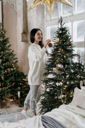 Beautiful young adult woman standing in room with  decorated christmas tree, spending new year holidays at home, standing in room with cozy winter interior and smiling wide