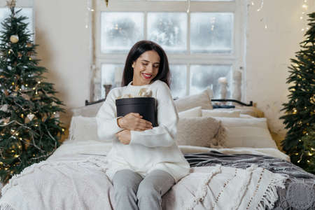 Happy young adult woman spending new year holidays at home, holding present box in hands, sitting on bed in cozy bedroom and smiling wide