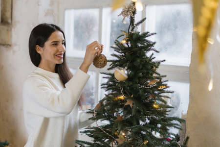 Happy and smiling young adult girl spending christmas holidays at home, decorated new year tree, standing at cozy room in house with winter interior