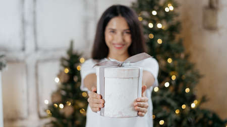 Panoramic view of blurred and dreamy young adult girl holding present box in hands, showing gift, standing in room with decorated christmas tree, spending new year holidays at home