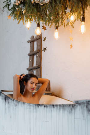 Beautiful, dreamy young adult woman spending weekend at home, taking bath with closed eyes in cozy white bathroom interior