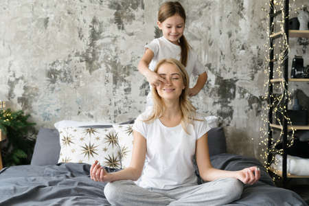 Smiling mother sitting on bed in meditating pose while she little daughter touching her nose. Mom and kid spending morning together at home. Concept of peaceful, tranquility and mental health 版權商用圖片