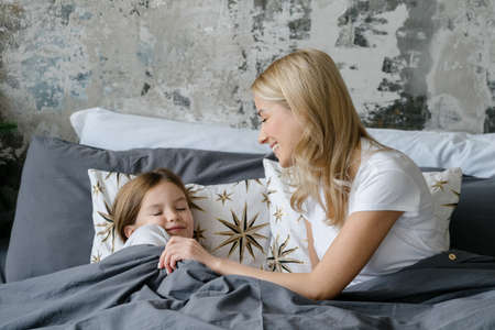 Happy mother cover with blanket her smiling daughter while she sleeping, lying in comfort bed. Woman and little girl spending free time together at cozy home