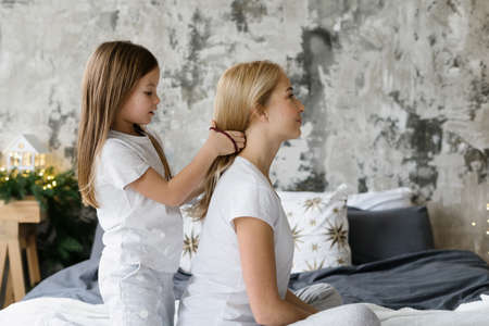 Profile view of little daughter braids hair and making hairdo for her smiling mother. Mom and kid girl playing together, sitting on bed and spending morning at home