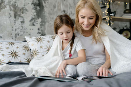 Concept of learning and hobby. Happy mother reading book with her smiling daughter while they sitting on comfort bed under plaid or blanket. Family spending weekend together at home