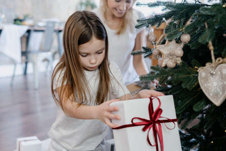 Concept of traditional winter holidays. Calm little girl holding present box in hands, sitting near christmas tree while her mother smiling, decorating room and preparing for new year