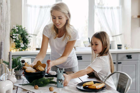 Little daughter serving food for breakfast together with loving mother. Woman and girl in pajamas putting plate and home decor on dinner table, family spending morning on kitchen