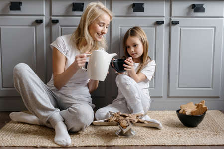 Full length view of happy mother pouring tea in cup of her smiling daughter, sitting on kitchen floor, having breakfast and spending weekend together at home