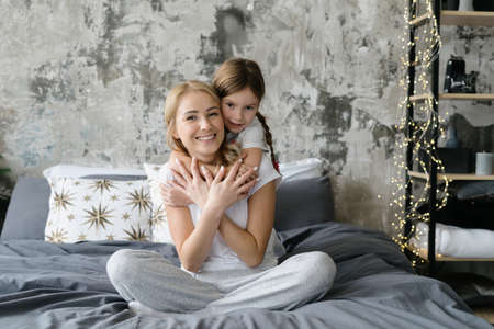 Single mother hugging with happy daughter, sitting on bed in sleepwear, spending morning together at home. Full length view of woman and girl cuddle to each other and smiling wide