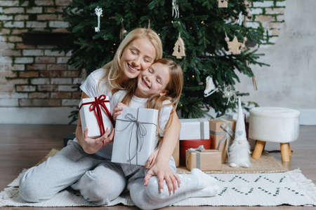 Merry christmas and happy new year. Caring and loving mother hugging her smiling daughter, holding gifts. Mom and daughter sitting near fir tree with presents in hands, spending time together at home