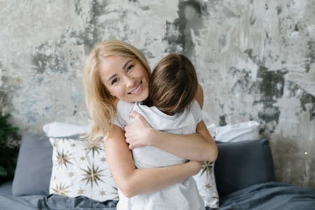 Concept of tenderness and happy motherhood. Portrait of loving mother hugging her cheerful daughter, looking at camera and smiling wide. Single mom and kid spending morning together at home 版權商用圖片