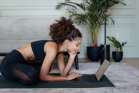 Online sport training concept. Thoughtful adult sporty afro american woman watching yoga exercise on internet app at modern laptop computer, preparing for workout at home 版權商用圖片