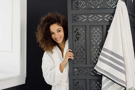 Natural beauty concept. Portrait of young happy adult afro american woman standing behind dressing screen in bathrobe, looking at camera and spending morning in bathroom