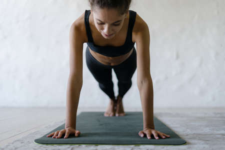 Serious afro american sporty and fit woman training at home, standing in plank pose on yoga mat, making sport exercise against white copy space wall. Concept of healthy lifestyle and strong body