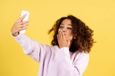 Charming young afro american woman making online video call on modern smartphone, talking with friends or family, sending air kiss, standing on yellow copy space background