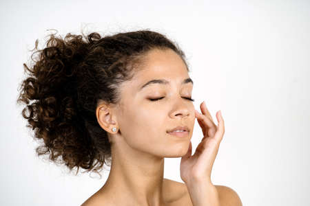 Moisturizing and pampering concept. Side view portrait of adult african american woman touching flawless fresh and pure skin , closed eyes, standing isolated on white background with copy space