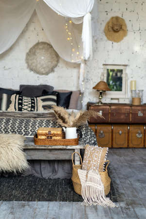 Vertical photo of wicker basket with plaid, pillows near wooden bench seat and home decor. Comfort bed in cozy bedroom with boho chic interior design