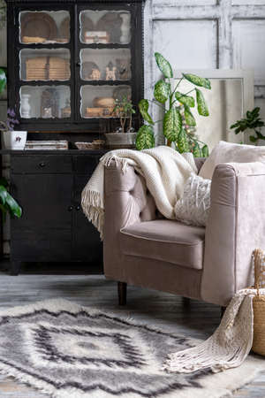 Vertical photo of black vintage chest of drawers near comfortable armchair with cozy plaid and cushions. Living room with furniture in house with ethnic carpet and modern interior design 版權商用圖片