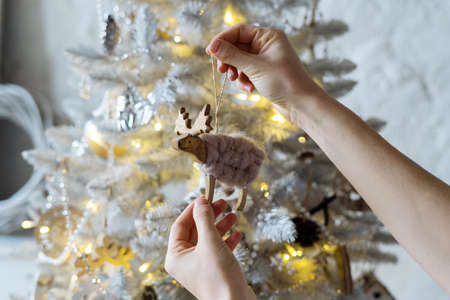 Cropped view of woman holding toy in hands against christmas tree in snow. Cozy interior with simple and craft new year decorations. Concept of preparation for winter holidays 版權商用圖片
